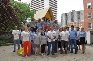 CCOC staff stand in front of a children's play structure in a sandbox.